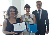 Status M -järjestön puheenjohtaja Leila Younis ja ohjelmakoordinaattori Maja Gergorić vastaanottamassa palkintoaan eli heiteltävää Catchbox-mikrofonia suurlähettiläs Risto Piipposelta.